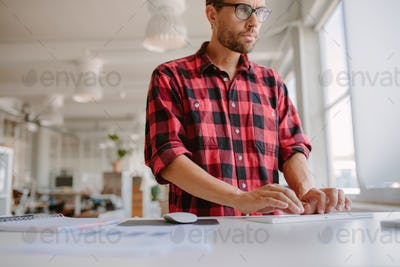 Businessman using computer in modern office.