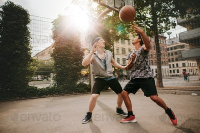 Two young men playing a game of basketball