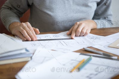 Female hands, working with a ruler and a drawing