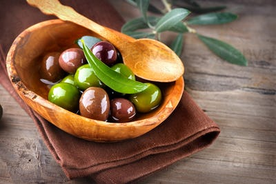 Olives and olive oil on wooden rustic table
