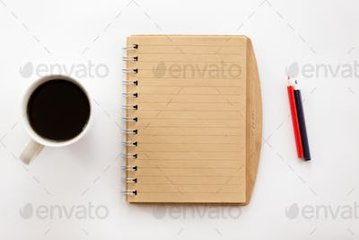 White office desk with a notebook and pencils, coffee