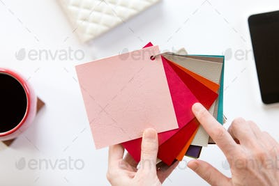 Female hands choosing a color fabric pattern
