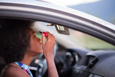 a young African-American woman makeup in the car