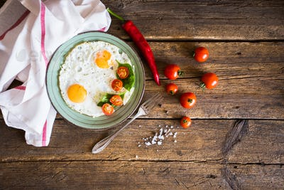 Scrambled eggs with tomatoes on wooden background
