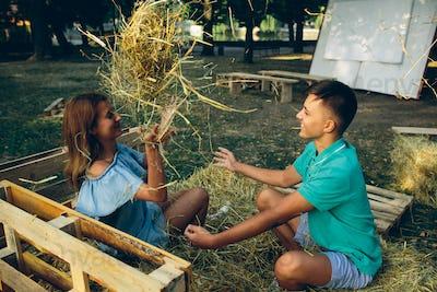guy and girl throwing hay