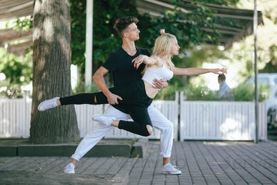 man and woman dancing in a park