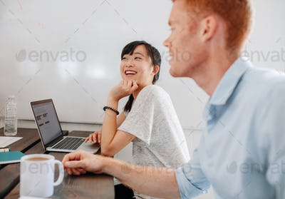 Two happy business people sitting at conference room
