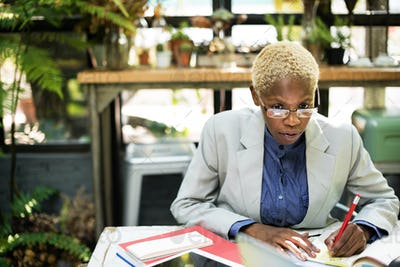 African Businesswoman Writing Paperwork Planning Strategy Workin