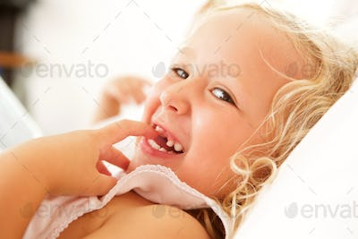 Beautiful little girl lying on bed and smiling