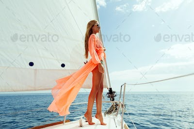 fashion model posing on yacht in sea with blue sky sunlight