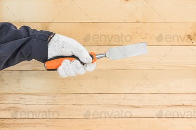 Hand in glove holding chisel