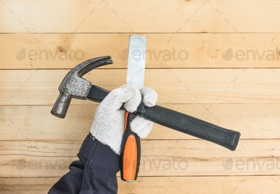 Hand in glove holding chisel and hammer