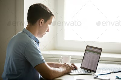 Profile portrait of young man working at desk with laptop