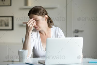 Portrait of a woman at desk with laptop, hand at forehead
