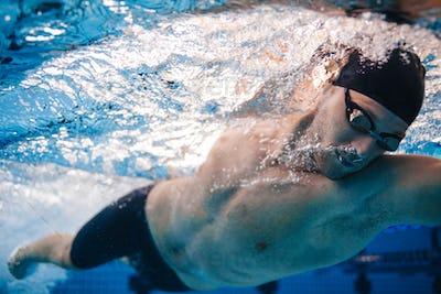 Professional male swimmer inside swimming pool.