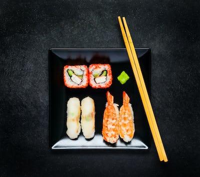 Sushi With Caviar and Sashimi on Black Plate with Chopsticks