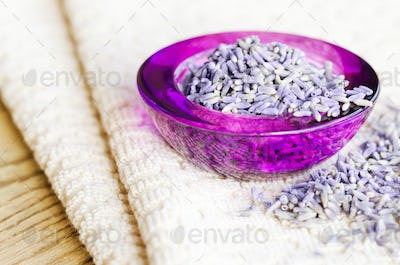 Dried lavender flowers in purple glass on fabric
