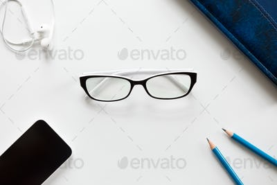 White office desk with glasses, pencils, earphones and mobile