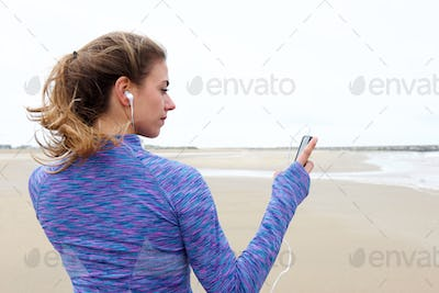 Beautiful woman holding cellphone with headphones