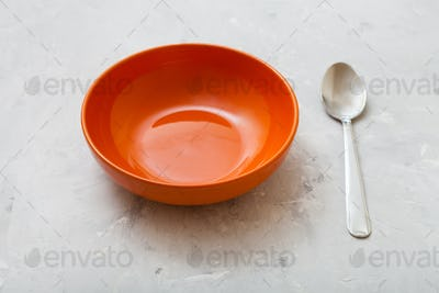 orange bowl and steel spoon on gray concrete plate
