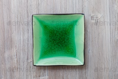 above view of green square saucer on gray table