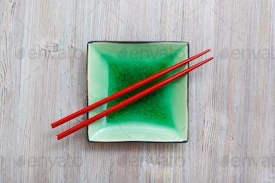 above view square saucer with chopsticks on gray