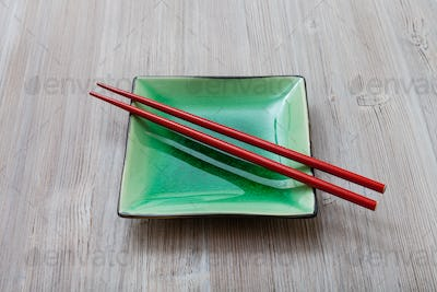 green square saucer with red chopsticks on gray