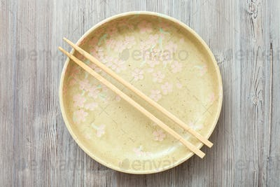 top view of yellow plate with chopsticks on gray