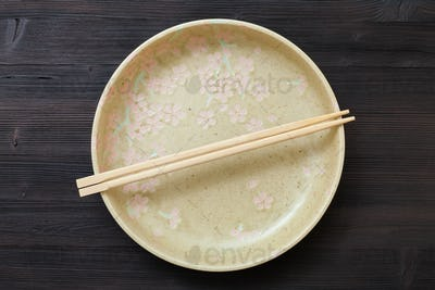 top view of yellow plate with chopsticks on brown