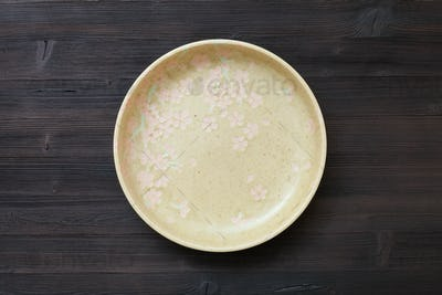 top view of green plate on dark brown table