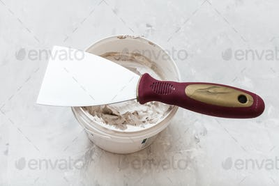 metal spatula on tube with putty