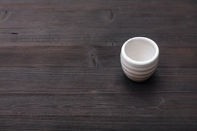 white cup for sake on dark brown wooden table