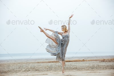 Woman ballerina in long dress dancing on the beach
