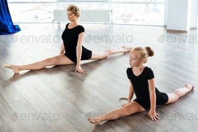 Little girl ballerina and teacher doing twine in ballet class