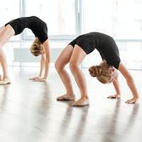 Graceful little ballerina and her teacher exercising in ballet studio