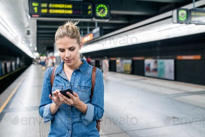 Woman at the underground platform with smartphone texting