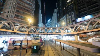 Illuminated street of Hong Kong with rails and pedestrian bridge