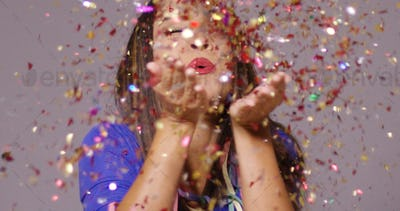 Cute young woman blowing confetti