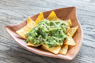 Guacamole with tortilla chips on the wooden background