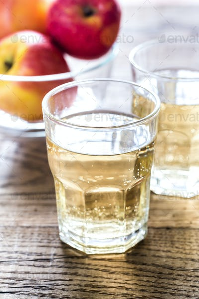 Two glasses of cider on the wooden background