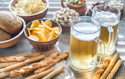 Two glasses of beer with appetizers