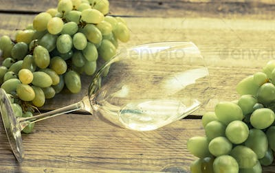 Glass of white wine with bunch of grape