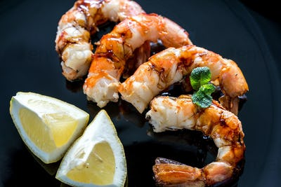 Fried shrimps with lemon wedges on the black background