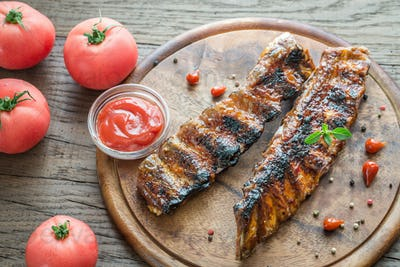 Grilled pork ribs with tomatoes on the wooden board