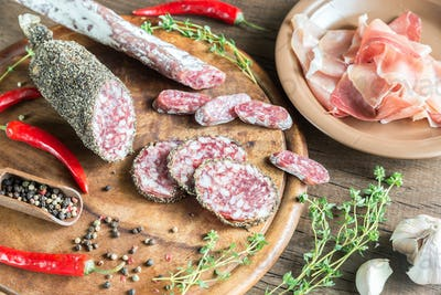 Slices of saucisson, jamon and salami on the wooden board