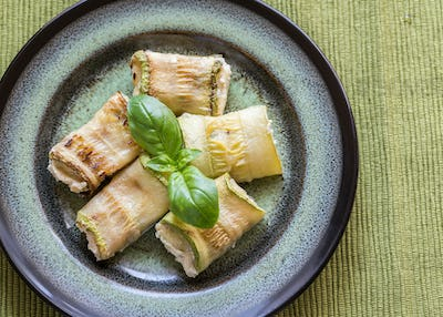 Portion of baked zucchini rolls stuffed with cheese