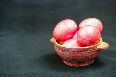Colorful eggs in clay bowl