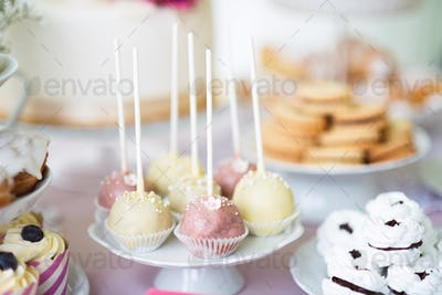 Cake pops on cakestand, meringues and cupcakes. Candy bar.