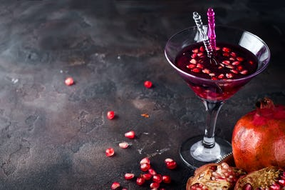Pomegranate, cut into sections on a metal dish in the background of the shot glasses