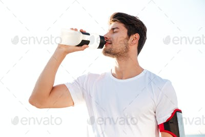 Thirsty athlete drinking water after workout